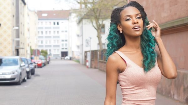 Model Janay flowers with pink dress and custom Hair By Mahogany unit with dark roots and green extensions.